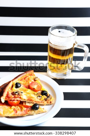 Sliced pizza served with beer on  striped background - stock photo