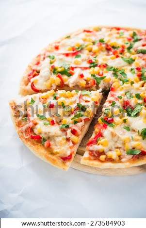 Sliced pizza with mozzarella cheese, chicken, sweet corn, sweet pepper and parsley on white background close up. Italian cuisine. - stock photo
