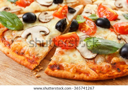 Sliced Pizza with mushrooms, olives and tomatoes. Basil, rosemary and fresh vegetables. Freshly homemade  - stock photo