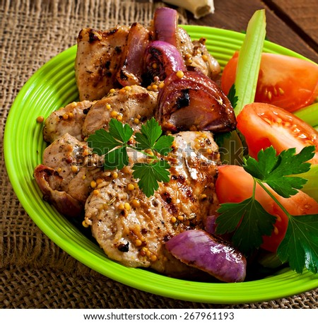 Sliced pork grilled with vegetables on green brown plate - stock photo