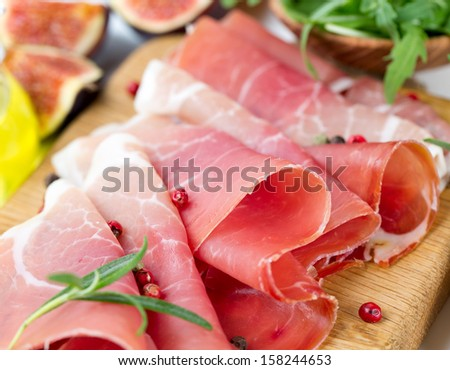 sliced prosciutto and vegetables - stock photo