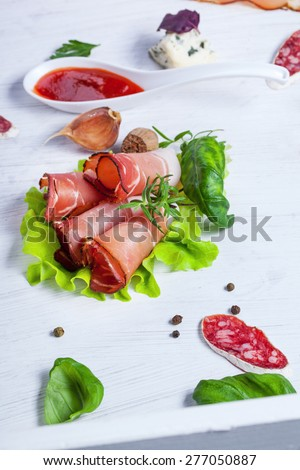 Sliced prosciutto in white wooden background - stock photo