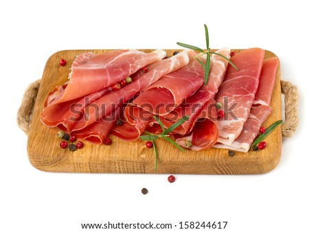 sliced prosciutto on a wooden board isolated on white background - stock photo