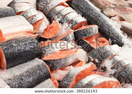 Sliced raw, not cooked salmon, red fish, lying in the ice on the counter in the supermarket. Fresh fish - stock photo