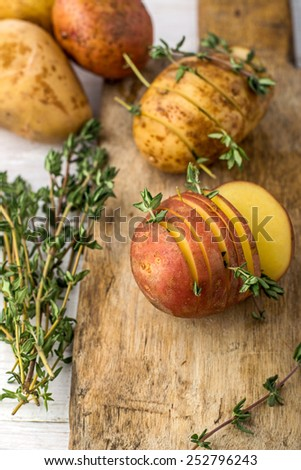 Sliced raw potatoes with sprigs of thyme, sea salt and butter before baking in the oven. selective Focus - stock photo