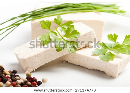 sliced raw tofu with parsley, salt and pepper on white plate - stock photo