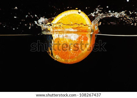 Sliced ripe orange falling into the water with a splash on a dark background - stock photo