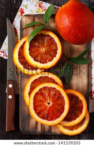Sliced ripe Sicilian orange on an old cutting board. - stock photo