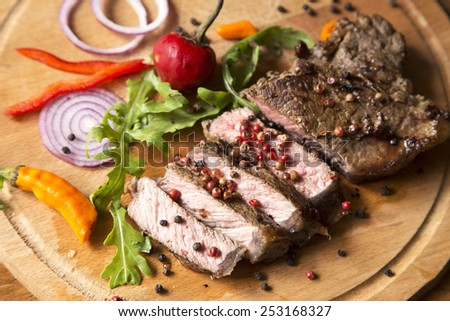 Sliced roast beef with vegetables on a wooden plate - stock photo