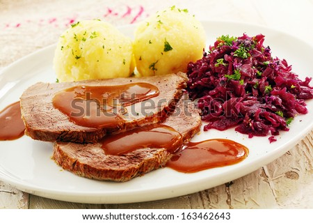 Sliced roast cap of rump topped with a rich brown gravy and served with sauerkraut and potato for a traditional German meal - stock photo