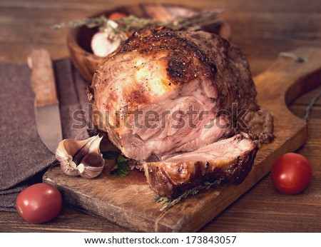 Sliced roasted pork with spices on wooden board - stock photo