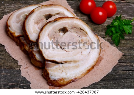 Sliced roasted roll pork loin with spices and fresh vegetables on a wooden background - stock photo