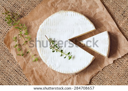 Sliced round camembert cheese traditional milk creamy dairy product with thyme on vintage parchment. Rustic style and natural light. Top view. Rustic sacking textile background. - stock photo