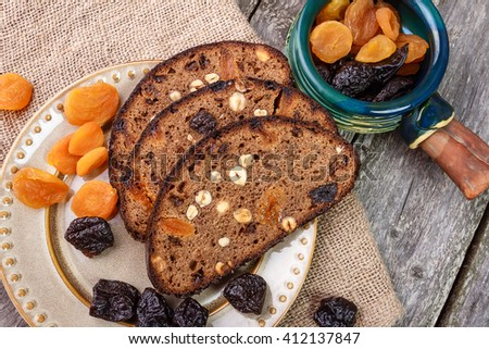Sliced rye bread with prunes, dried apricots and hazelnut on old rustic table. Top view. - stock photo
