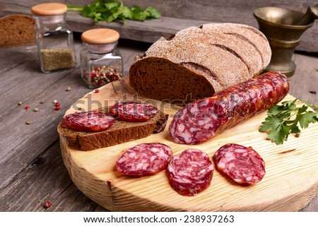 Sliced salami and bread on a cutting board - stock photo