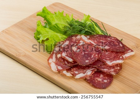 Sliced Salami with rosemary on the wooden bckground - stock photo