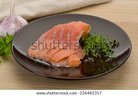 Sliced salmon sashimi on the board with herbs  - stock photo