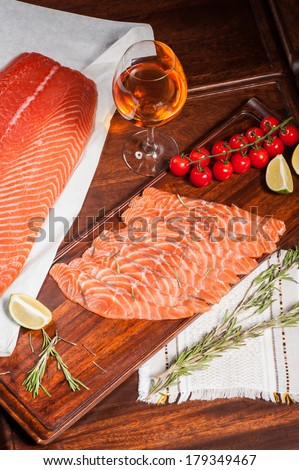 Sliced salted salmon on wooden board served with white wine - stock photo