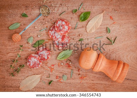 Sliced sausage salami with herbs and spices ,thyme, rosemary, saffron,basil, pepper, and oregano on the teak wood table . - stock photo