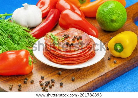 Sliced Sausage with vegetables and herbs around on the table - stock photo