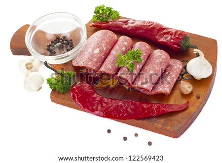 sliced smoked sausage isolated on white background with parsley and garlic - stock photo