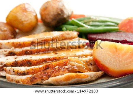 sliced turkey with roasted potatoes, sugar beets, yams and green beans. a traditional holiday meal - stock photo