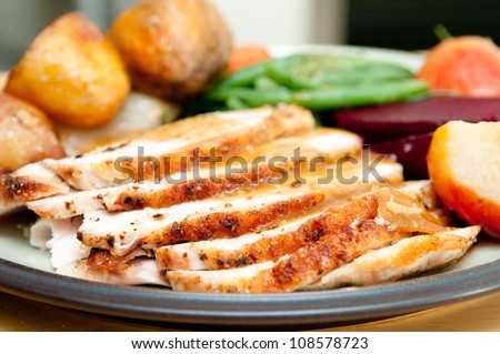 sliced turkey with roasted potatoes, sugar beets, yams and green beans perfect for Christmas dinner and Thanksgiving meals - stock photo
