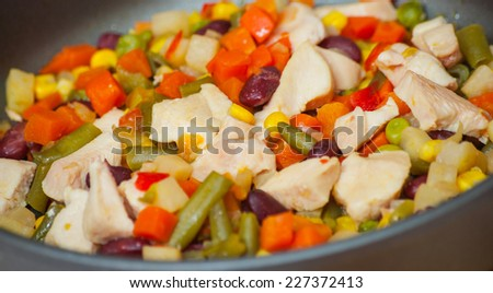 Sliced vegetables and chicken breast in pan - stock photo
