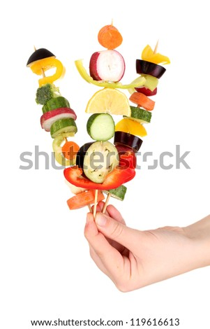 Sliced vegetables on wooden picks holding in hand isolated on white - stock photo