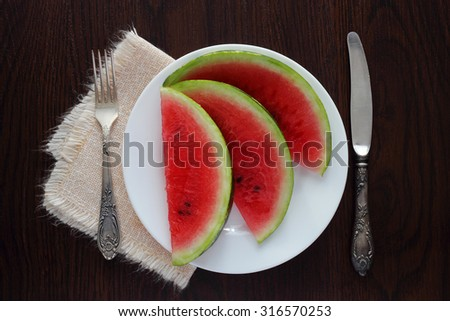 Sliced watermelon on white plate with knife and fork on wood background - stock photo