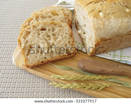 Sliced white bread with spelt flour from baking tin  - stock photo
