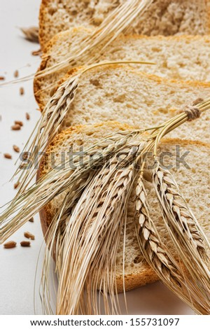 slices bread and ears of corn on white background - stock photo