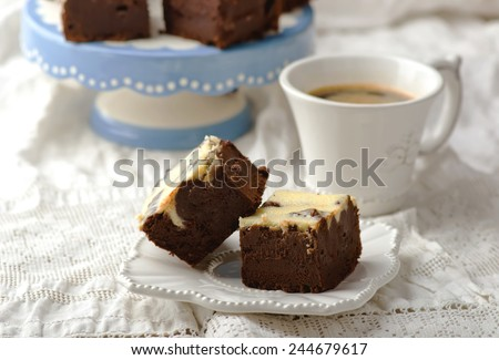 slices chocolate brownie on a white saucer and a cup of coffee ...