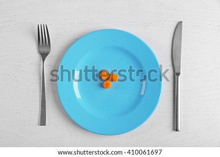 Slices of baby carrots in a blue plate on white table.. Top view. - stock photo