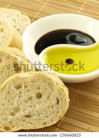 Slices of baguette and bowl of oil - stock photo