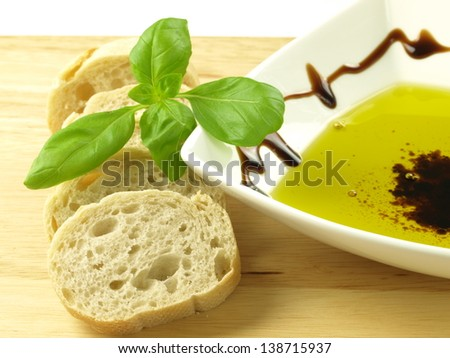 Slices of baguette with olive oil and basil - stock photo