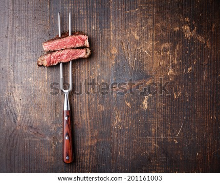 Slices of beef steak on meat fork on dark wooden background - stock photo
