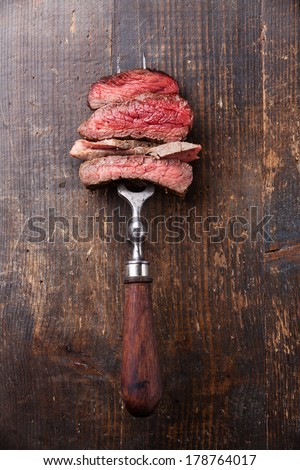 Slices of beef steak on meat fork on wooden background - stock photo