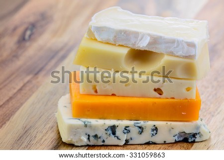 Slices of blue cheese, brie cheese, swiss cheese, red cheddar, maasdam cheese on the wooden background. - stock photo