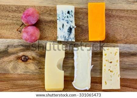 Slices of blue cheese, brie cheese, swiss cheese, red cheddar, maasdam cheese with grapes on the wooden background. - stock photo
