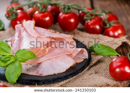 Slices of boiled ham (close-up shot) with fresh herbs - stock photo