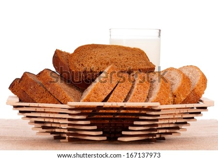 Slices of bread on a decorative dish with milk over white background - stock photo
