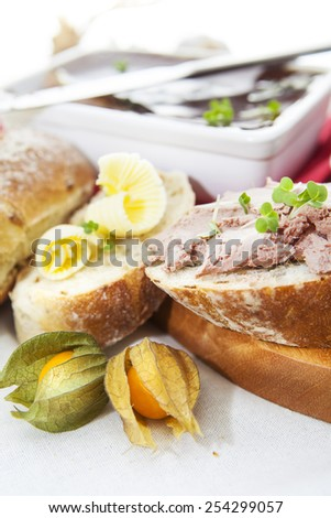 Slices of bread, pate and butter on wooden cutting board with dish of pate, knife and physalis over white cloth  - stock photo