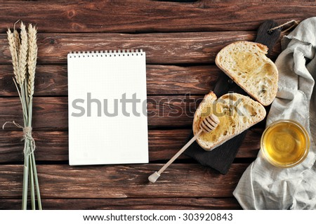 Slices of bread with honey on wooden Boards on wooden background. Near the slices of bread a blank notebook and ears of wheat. Copy space. Free space for text. Top view. Breakfast - stock photo