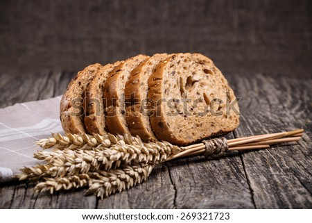 Slices of bread with rye on a wooden background. - stock photo