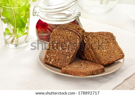 Slices of brown bread on linen napkin with mint and plum compote - stock photo