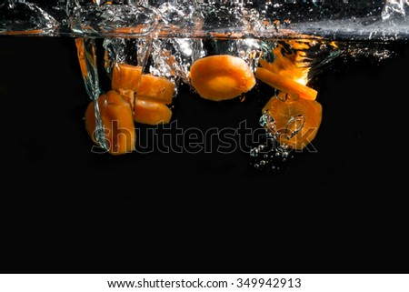 slices of carrots falling into water - stock photo