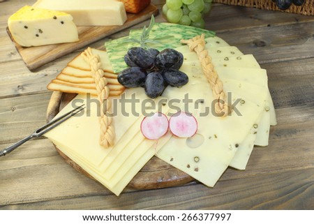 Slices of cheese with grapes, radishes and fork - stock photo