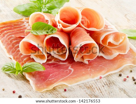 Slices of cured ham on a wooden table . Selective focus - stock photo