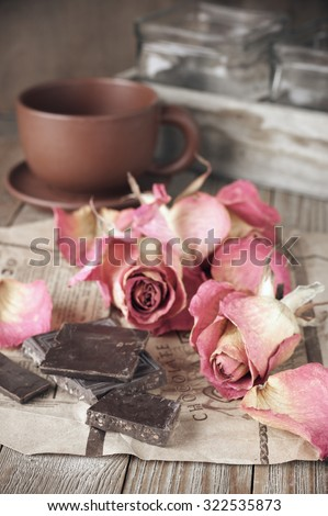 Slices of dark chocolate on rough paper, dried pink roses heads and coffee cup on wooden table. Shallow DOF, focus on chocolate. - stock photo